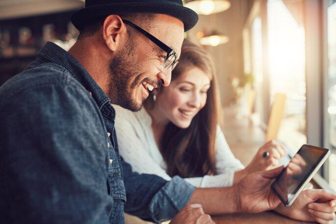 Pareja de novios revisando su lista de tareas en tablet