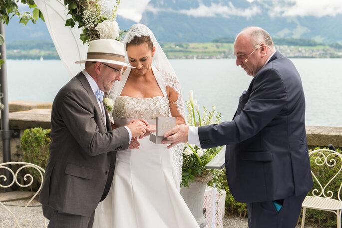 Der Trauredner Hochzeitszeremonien mit Stil Jan Euskirchen reicht dem Bräutigam die Ringe, die Braut schaut auf das Ringkästchen.