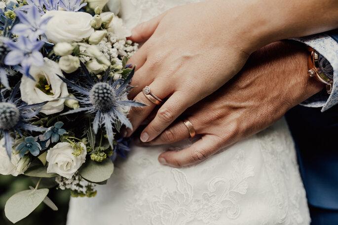 Brautpaar. Hände des Brautpaares mit Brautstrauss und Ringen