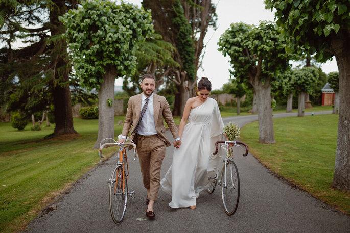 Brautpaar mit Fahrrädern laufend