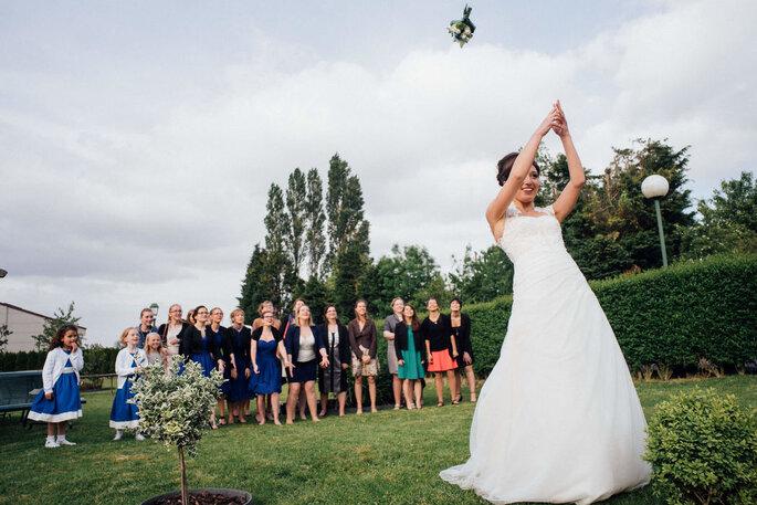 La mariée effectue le célèbre lancé de bouquet, ses invitées l'attendent avec joie