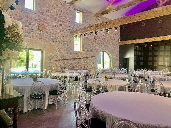 Salle de réception pour un mariage avec des poutres apparentes et des mur de pierres