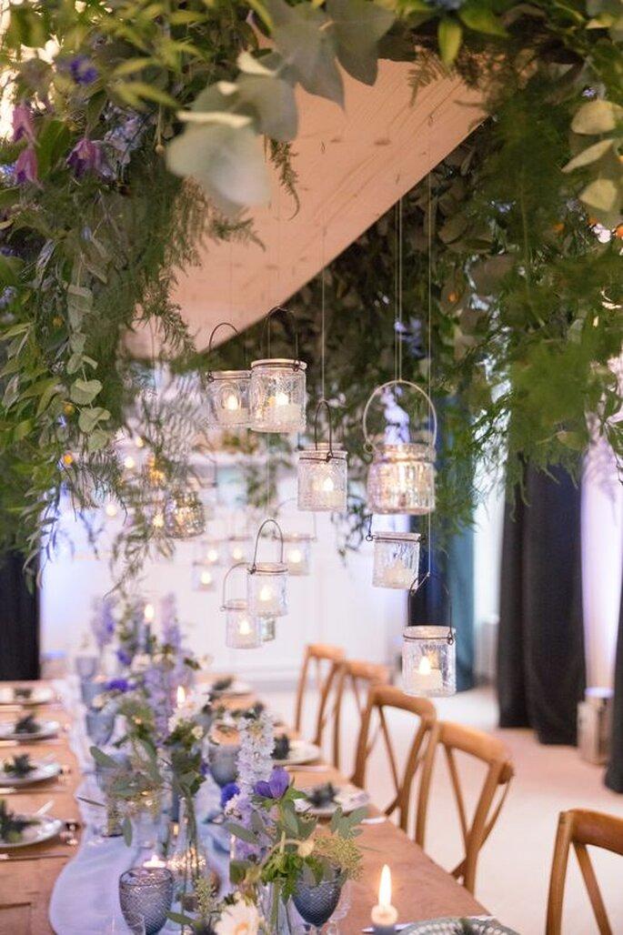 Le Domaine des Cormellas et sa table bohème décorée de bougies, de fleurs violettes, de chaises en bois, de plantes, et de bougeoirs suspendus