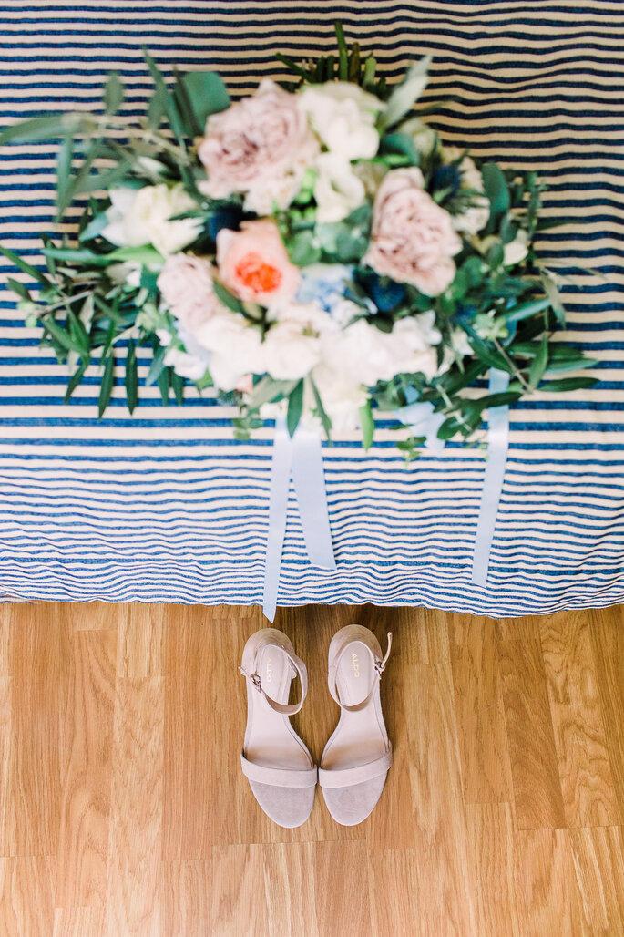 bouquet de noiva em cima de uma toalha de riscas com os sapatos de noiva em baixo