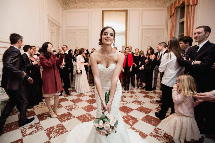 une mariée dans un sublime intérieur carrelé, prête à jeter son bouquet à ses invités au Château de Santeny