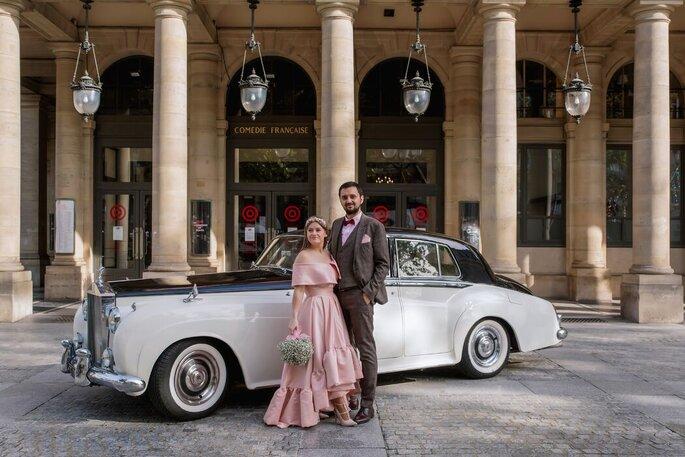Un couple prend la pose devant une voiture de collection.