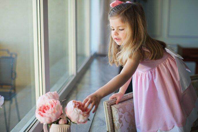 menina loura com vestido cor de rosa laço atrás e laço no cabelo festa casamento