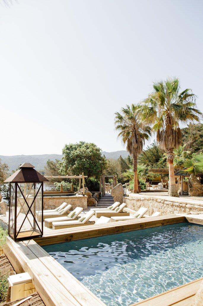 Piscine, transats, palmiers en Corse avec vue sur les îles
