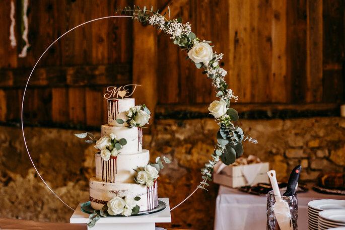 Die Hochzeitstorte in blumiger Dekoration, Foto von Hüttner Fotografie.