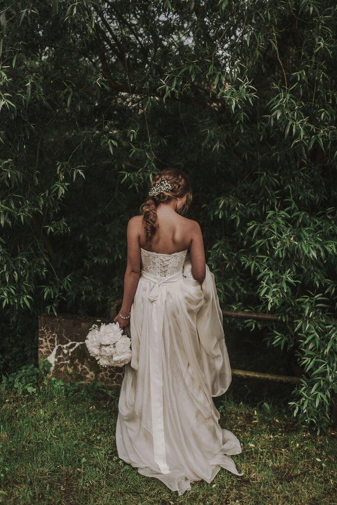 Blick auf Braut von hinten im Grünen