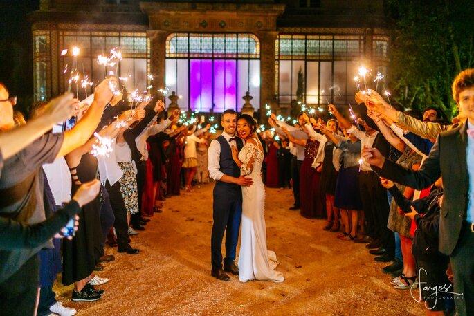 Deux mariés enlacés à la lueur des bougies, sous une haie d'honneur devant le Château de la Beaumetane