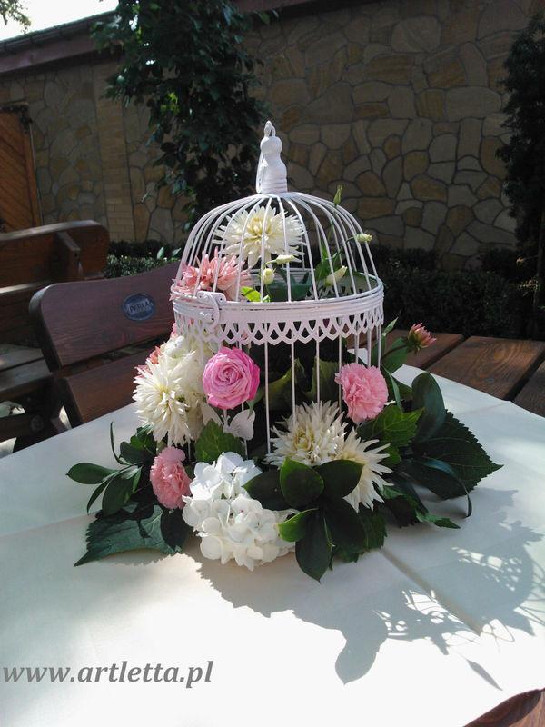 letnia kompozycja z ogrodowych kwiatów:piwoni,dali I hortrnsji w białej ozdobnej klatce.