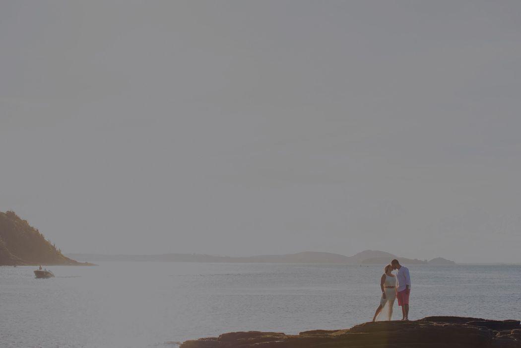 paisagem de praia com noivos se beijando