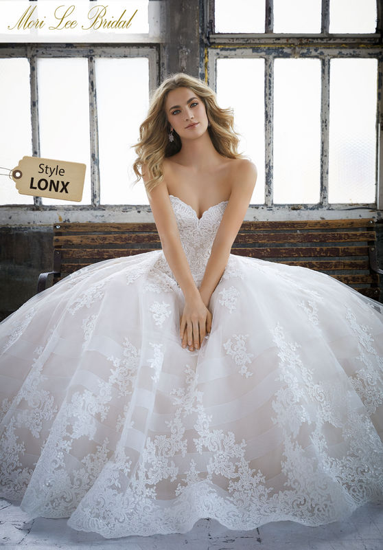 Style LONX  Kimberley Wedding Dress  Princess Ballgown featuring a Sweetheart Neckline and Alençon Lace on Tulle. A Wide Hemline and Decorative Horsehair Bands Trim the Skirt. A Zipper Back Closure Trimmed in Covered Buttons Complete the Look. Available in Three Lengths: 55″, 58″, 61″. Colors Available: White, Ivory, Ivory/Crème