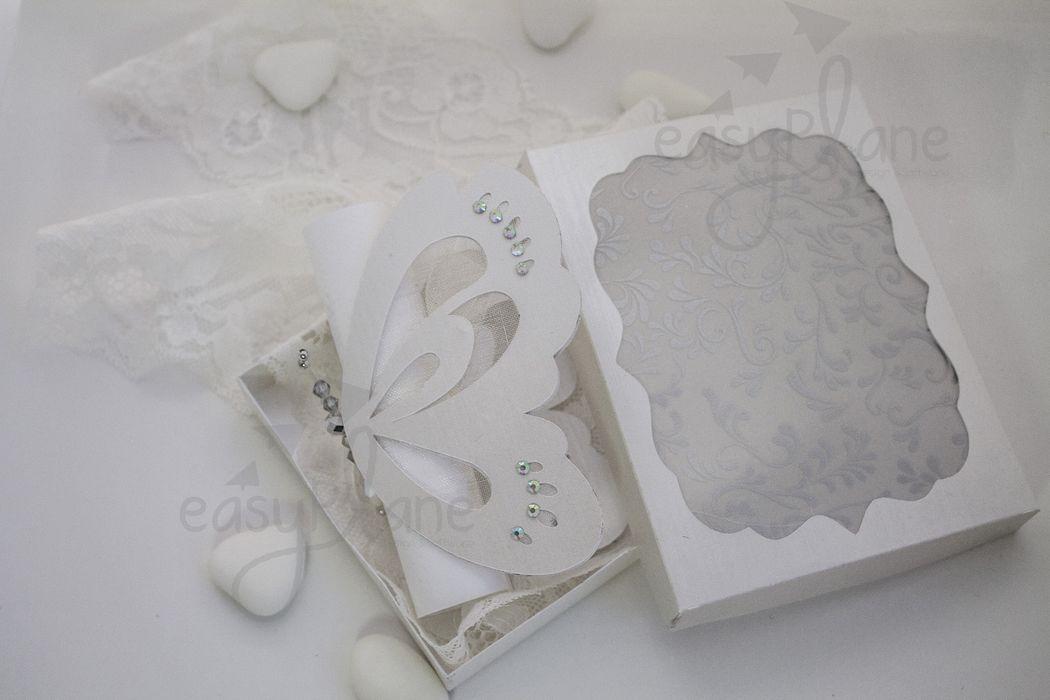 Una delicata partecipazione in scatola che al suo interno nasconde un'eterea farfalla realizzata in tulle e preziosa carta satinata. L'invito e l'annuncio sono racchiusi in un'elegante pergamena