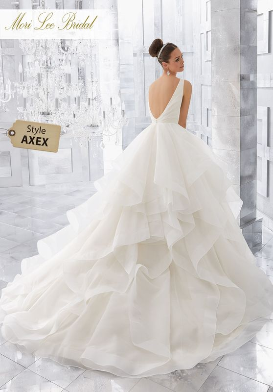 Style AXEX Milly Wedding Dress  Light and Airy, this Stunning Flounced Organza Ball Gown with Wide Horsehair Edging Features a Plunging V-Neck and Open V-Back. Illusion Insets Along Sides . Available in Three Lengths: 55″, 58″, 61″. Colors Available: White, Ivory.