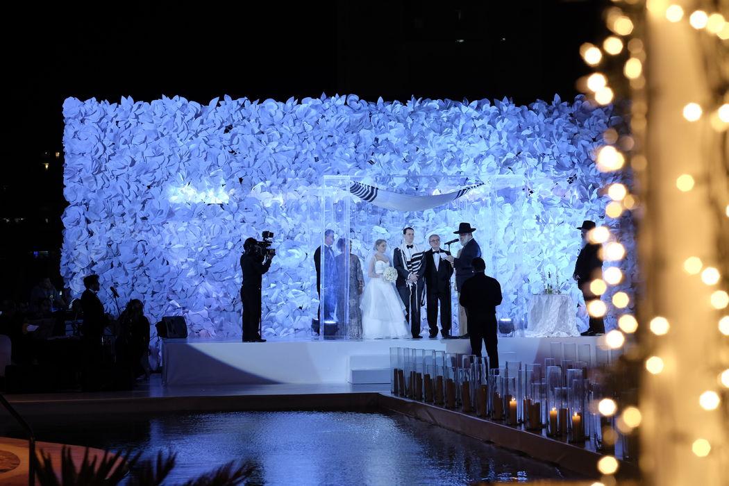 Ceremonia Religiosa.  Pared en grandes  flores de fantasía y velones que se suman romanticismo al momento.