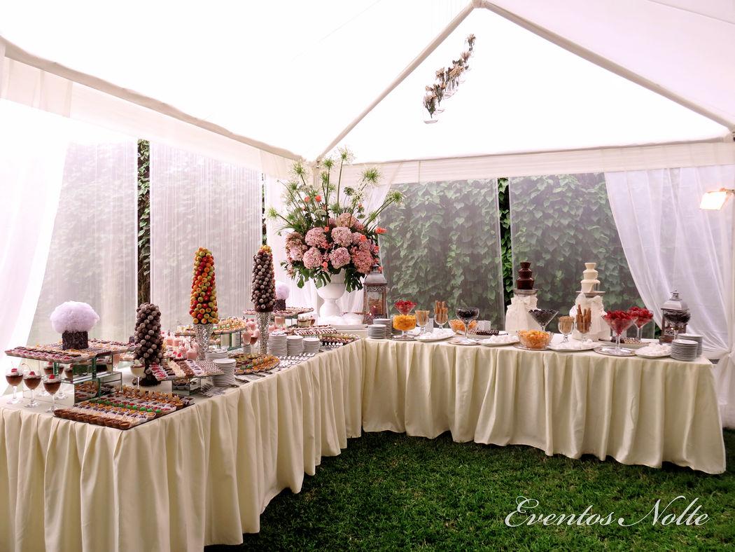 Mesa de dulces con 2 piletas de chocolate.