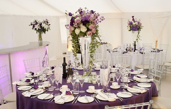 Tall Table Decorations. Tall clear glass vases topped with co-ordinating purple summer flowers including scented stocks and sweet peas