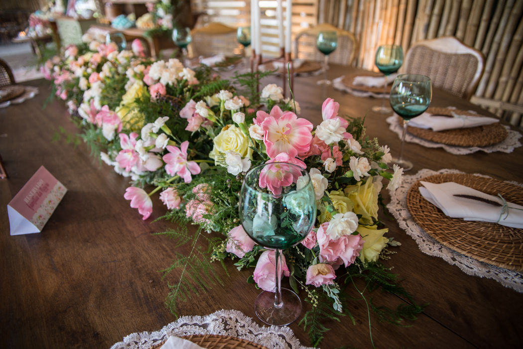 Na mesa posta um lindo caminho de flores cheio de tulipas e rosas