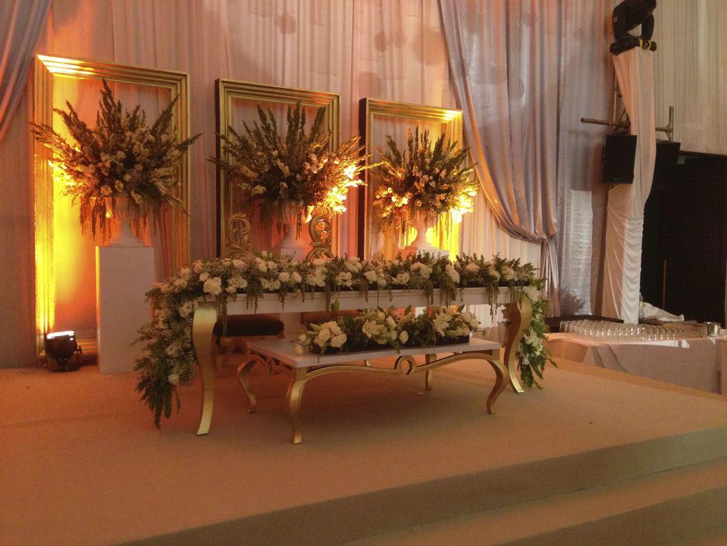 Conjunto de mesa Pata de Cuerno en laca blanca y patas doradas para mesa de novios, con un arreglo floral.