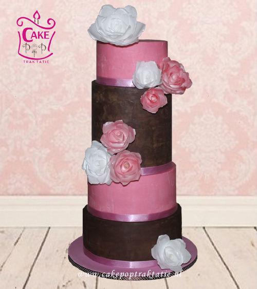 Deze Bruidstaart heeft geen fondant. De hele taart is bedekt met chocolade ganache, puur en roze gekleurde witte chocolade. De bloemen zij gemaakt van ouwel, eetbare papier. Voor ongeveer 70 personen.