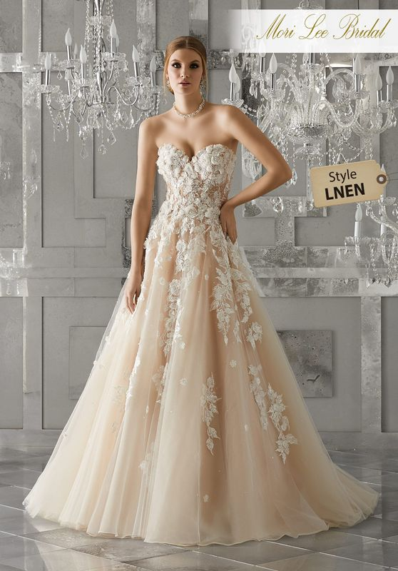 Style LNEN Meadow Wedding Dress  Strapless Soft Tulle Ball Gown featuring Sweetheart Neckline and Embroidered Lace Appliqués. Three Dimensional Flowers Accent the Bodice and Cascade Down the A-Line Skirt. Covered Button Details Along the Back. Colors Available: White, Ivory, Ivory/Nude.