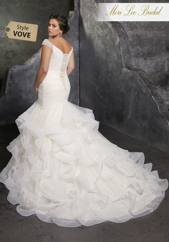 Style VOVE Kori Wedding Dress  Asymmetrically Draped Tulle Creates a Figure Flattering Mermaid Silhouette with Off-the-Shoulder Beaded Cap Sleeves. A Flounced Full Skirt and Corset Style Back Complete the Look. Available in Three Lengths: 55″, 58″, 61″. Colors Available: White, Ivory, Ivory/Champagne