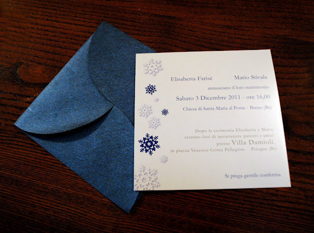 Partecipazione per matrimonio invernale a tema fiocco di neve, su cartoncino perlato e busta con chiusura  a fiore in carta broccata blu.