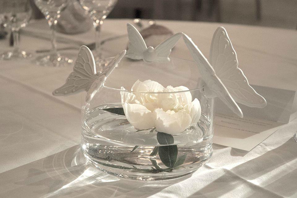 Papillon vole et se pose délicatement sur le rebord de cette coupe en verre pour admirer les fleurs naturelles qui viendront embellir votre table.
