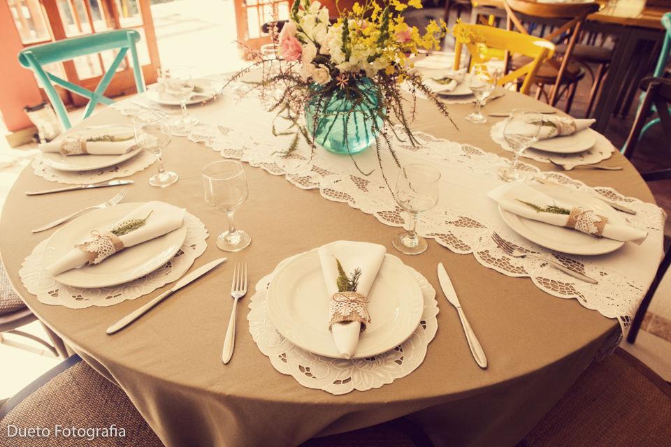 Na mesa dos convidados bordado inglês com arranjo floral delicado. Super romantiquinho.