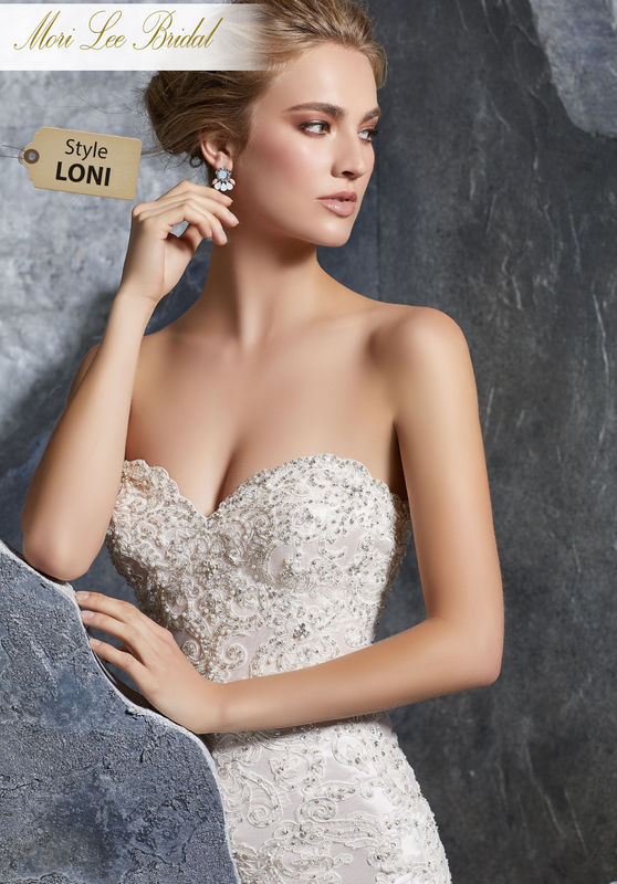 Style LONI  Kourtney Wedding Dress  Glamorous Sheath Gown Accented in Allover Crystal Beading and Metallic Embroidered Appliqués on Net. A Zipper Back Closure Trimmed in Covered Buttons Completes the Look. Available in Three Lengths: 55″, 58″, 61″. Colors Available: White, Ivory, Ivory/Blush