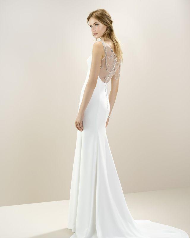 Изысканное платье прямого силуэта с декором на спинке в виде бус и камней.