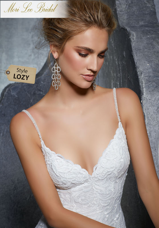 Style LOZY  Kiley Wedding Dress  Fitted Sheath Gown Featuring a Patterned, Embroidered Net Over Chantilly Lace with Beaded Straps. A Deep V-Neckline and Open Back Complete the Look. Available in Three Lengths: 55″, 58″, 61″. Colors Available: White, Ivory