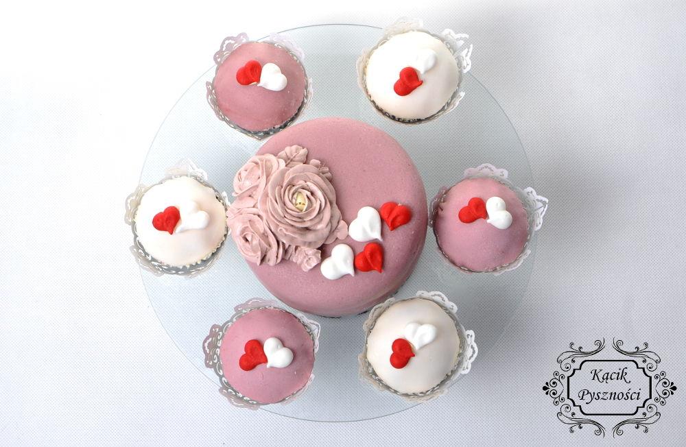 Torcik z puszystym biszkoptem waniliowym, masą porzeczkową i słodkim lekkim jak puch kremem maślanym na bazie bezy szwajcarskiej. Całość przykryta różową masą cukrową, przybrana trzema różami i małymi słodkimi serduszkami.