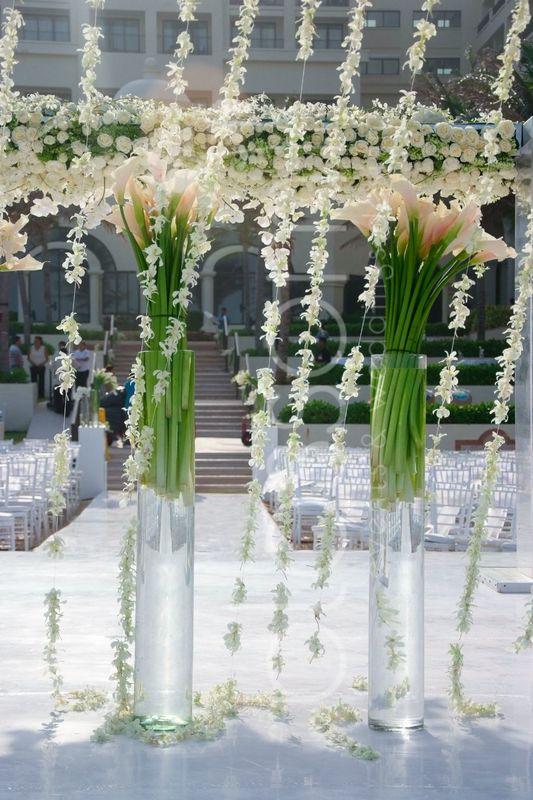 Cortinas de orquideas caen de este hermosa huppa llenas de flores blancas y alcatraces.