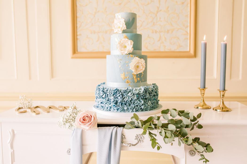 Bruidstaart met blauw gemarmerd fondant en een kleine goud decoratie