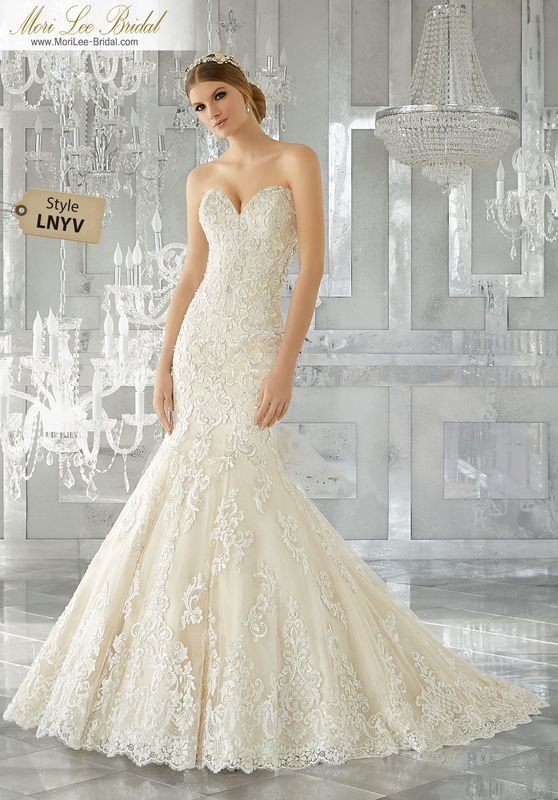 Style LNYV Melrose Wedding Dress  Breathtaking and Timeless, This Stunning Fit and Flare Wedding Gown Features Frosted, Embroidered Appliqués on Tulle Over Sparkle Net. A Wide Scalloped Hemline and Sheer Back with Exposed Boning Complete the Look. Shown with Detachable Tulle Over Sparkle Net Train (not included), Sold Separately as Style# NXOEN. Available in Three Lengths: 55″, 58″, 61″. Colors Available: White, Ivory, Ivory/Light Gold.