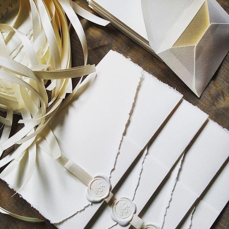 Il Calligrafo - Inviti in carta Amalfi su foglio unico avorio con sigillo e nastro in tinta. Provvisti di bustina, medesima carta e colore, contenente informazioni dettagliate per gli ospiti.