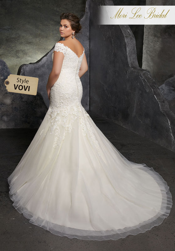 Style VOVI Kariana Wedding Dress  Figure Flattering Tulle Mermaid with Crystal Beading and Sculptured Lace Appliqués Along Bodice. A Romantic Off-the-Shoulder Neckline and Covered Buttons Along the Back Complete the Look. Colors Available: White, Ivory, Ivory/Champagne