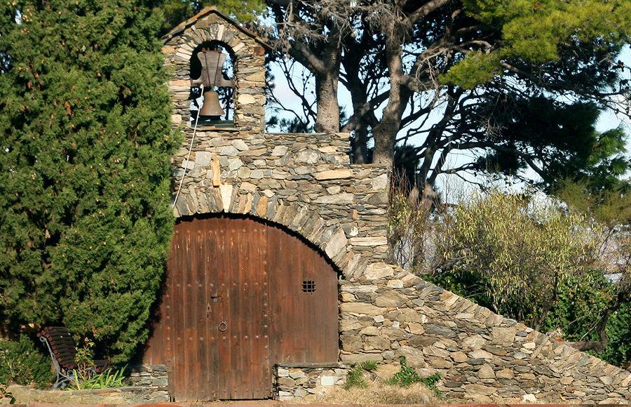 La capilla diminuta está ubicada entre la piscina y la pérgola, con un ciprés de guardián.