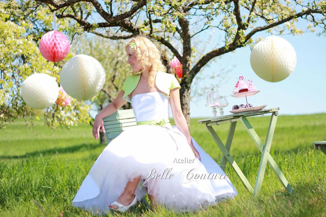 trägerloses, schlichtes Petticoat Brautkleid aus Dupiontaft, Tea-Length, farbiger Akzent durch Satingürtel mit Schleifchen und Kurzarmbolero