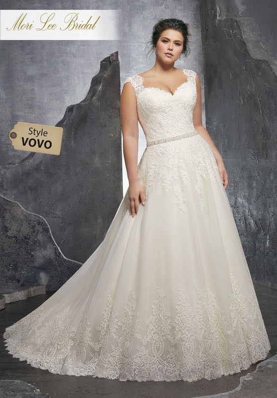 Style VOVO Kenley Wedding Dress  Figure Flattering A-Line Wedding Dress Featuring an Alençon Lace Appliqués on The Sweetheart Bodice and Soft Tulle Ball Gown Skirt. Delicate Cap Sleeves and a Wide Scalloped Hemline and Diamanté Waistline Trim Complete the Look. Available in Three Lengths: 55″, 58″, 61″. Colors Available: White, Ivory, Ivory/Champagne
